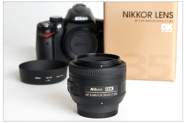 Nikon 35mm f/1.8G DX Nikkor lens with lens shade, box and Nikon D5000 camera
